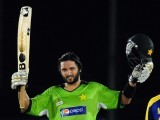 Pakistan cricket captain Shahid Afridi raises his bat and helmet in celebration after scoring a century. PHOTO: AFP/FILE