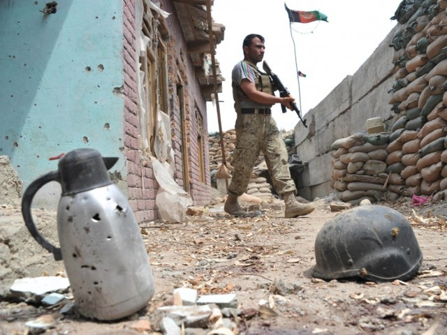 An Afghan security serviceman keep watch at a damaged police post following an airstrike in Bati Kot district in Nangarhar province on August 1, 2013. PHOTO: AFP