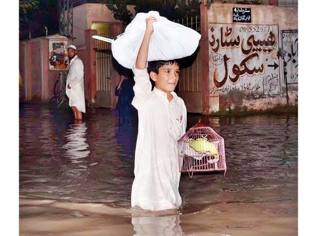 A youngster shifts his valuables to a safer place as floodwater enters Budhani area near Peshawar. PHOTO: APP