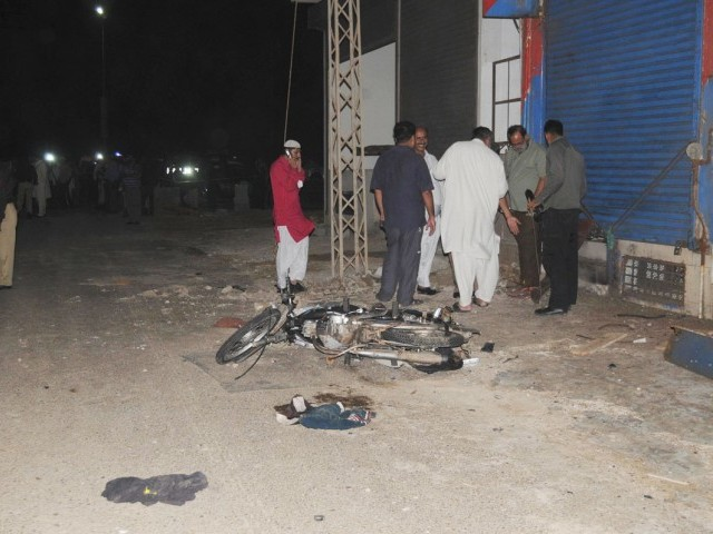 Officials gather outside a liquor store on Khayaban-e-Muslim after a blast. PHOTO: MOHAMMMAD NOMAN/EXPRESS