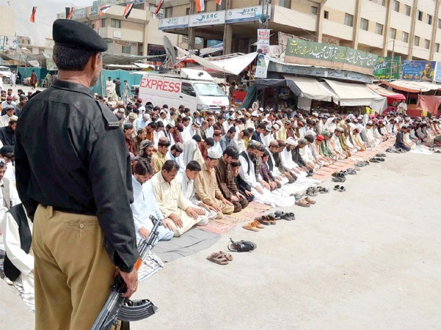 A policeman stands firmly at guard whilst Muslims say their prayers. PHOTO: FILE