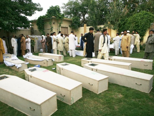 Relatives and colleagues gather near the caskets of victims killed in a suicide bomb attack before funeral ceremony at a police headquarters in Quetta August 8, 2013. PHOTO: REUTERS/FILE