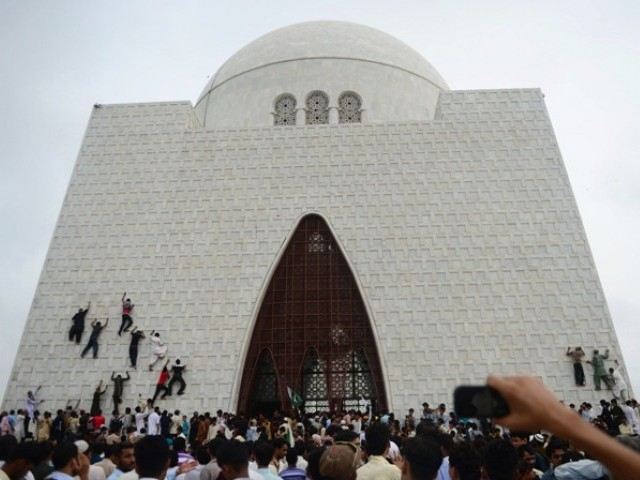 Pakistani youths climb the facade of Muhammad Ali Jinnah's mausoleum on August 14. PHOTO: AFP
