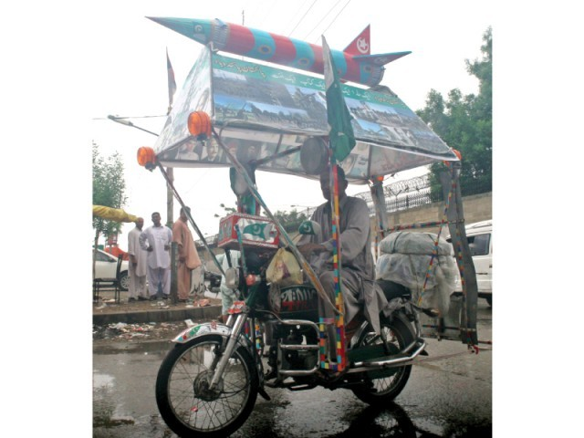 Lala Pakistani with his decorated bike carrying pictures of martyred army personnel and a model of Ghauri missile. PHOTO: ATHAR KHAN/EXPRESS
