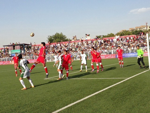 Afghanistan national footballers (in red) compete with Pakistan players (in green) during a football match in Kabul stadium on August 20, 2013. PHOTO: REUTERS/FILE