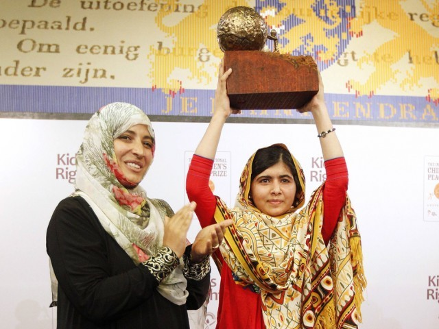 Malala Yousafzai raises a trophy she was given by Yemeni Civil Rights activist and 2011 Nobel Peace Prize winner Tawakkul Karman after being honored with the International Children's Peace Prize. PHOTO: AFP