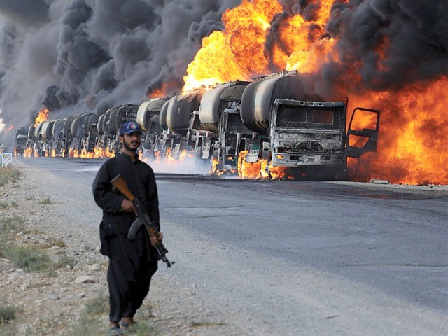 File photo of a policeman standing next to burning Nato supply oil tankers following an attack by gunmen. PHOTO: AFP/FILE