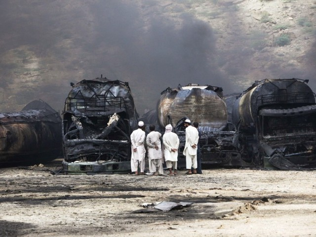 Men stand near damaged tankers of a NATO supply convoy after an attack a day earlier in Hub, about 25 km from Karachi, September 16, 2013. PHOTO: REUTERS