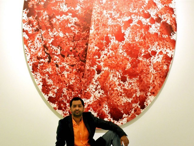 Artist Iman Qureshi poses next to his workon September 23, 2013 during the opening of his exhibition at the Macro Museum in Rome. PHOTO: AFP