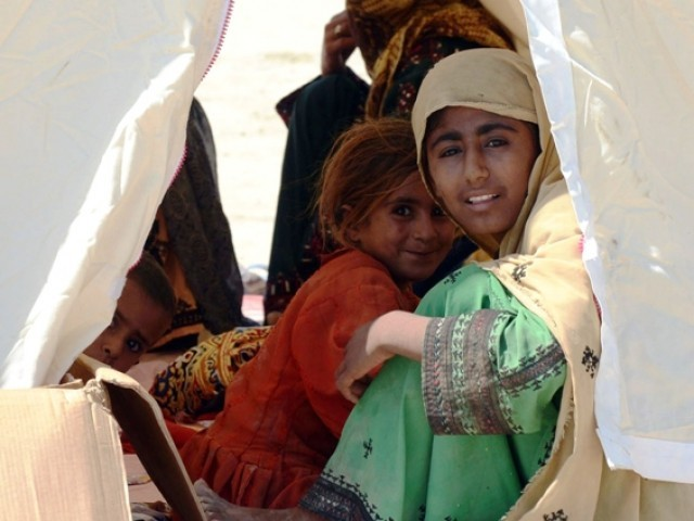A Pakistani earthquake survivor family sit in a tent near their collapsed mud houses in the earthquake-devastated district of Awaran on September 25, 2013. PHOTO: AFP