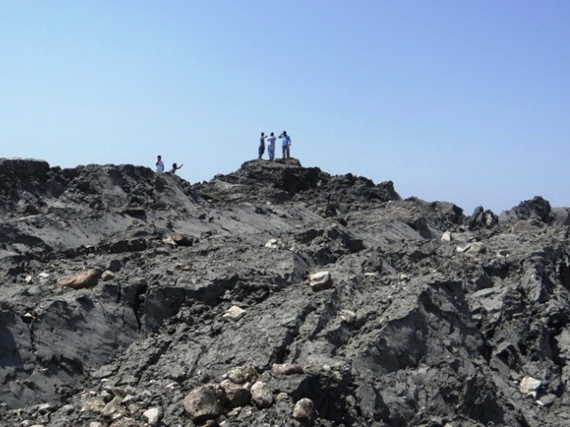 Locals climb to the top of the new Island. PHOTO: AFP