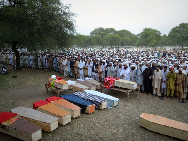 Relatives and residents offer funeral prayers for blast victims in Shabqader on September 29, 2013. PHOTO: AFP