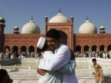 People greet each other after offering Eid prayers in Lahore October 16, 2013. PHOTO: REUTERS
