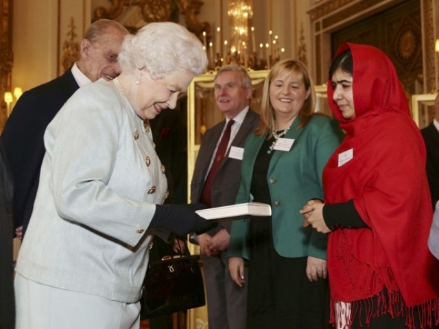 "Malala Yousafzai gives a copy of her book ""I am Malala"", to Britain's Queen Elizabeth during a Reception for youth, education and the Commonwealth at Buckingham Palace in London October 18, 2013.    PHOTO: REUTERS"