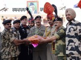 ndian Border Security Force (BSF) officiating Deputy Inspector General (DIG), Baby Joseph (L), BSF Commandant, Satish  Kumar (2L) along with BSF officers gives a gift to Pakistani Ranger Wing commander Asher Khan (C) on Diwali at the India-Pakistan Wagah Border on November 3, 2013. PHOTO: AFP