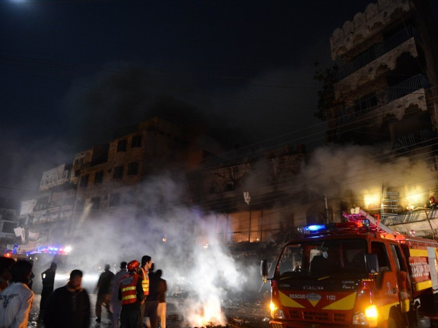 Pakistani rescuers and security personnel gather in front of a burning market after sectarian clashes near a mosque during the Shia procession in Rawalpindi on November 15, 2013. PHOTO: AFP