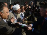 Senior minister Sirajul Haq (2nd L) hands over a memorandum to US consular official Christopher Allan Bacon (R) outside the consulate in Peshawar. PHOTO: AFP