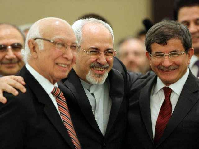 Iranian Foreign Minister Mohammad Javad Zarif (C) poses for a picture with his counterparts from Pakistan, Sartaj Aziz (L), and Turkey, Ahmet Davutoglu, during the opening session of a two-day ministerial conference of the Economic Cooperation Organisation (ECO), which groups 10 Asian and Eurasian countries, in Tehran on November 26, 2013. PHOTO: AFP