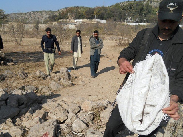 Security personnel examine the site of a sucide bombing in the Ibrahimzai area of Hangu district on January 6, 2014. PHOTO: AFP