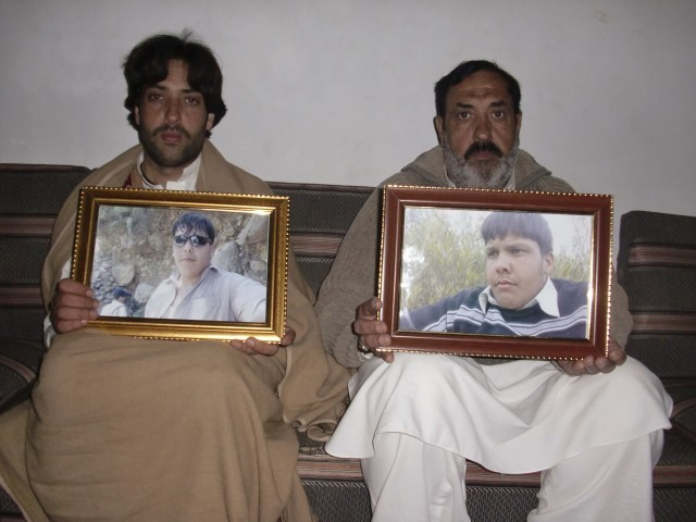 Mujahid Ali (R) and Mujtaba Hasan, the father and brother respectively of Aitizaz Hasan, pose for the camera with framed pictures of Hassan at their residence in Hangu district, bordering North Waziristan, January 10, 2014. PHOTO: REUTERS