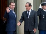 Ignored: French President Francois Hollande holds on warm shake between the once cold war enemies as Russia's Prime Minister Dmitry Medvedev charms the crowd at the Elysee Palace in Paris. PHOTO: AFP