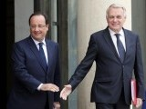 Miscoordination: French Prime Minister Hollande (L) misses a friendly shake with Jean-Marc Ayrault. PHOTO: AFP