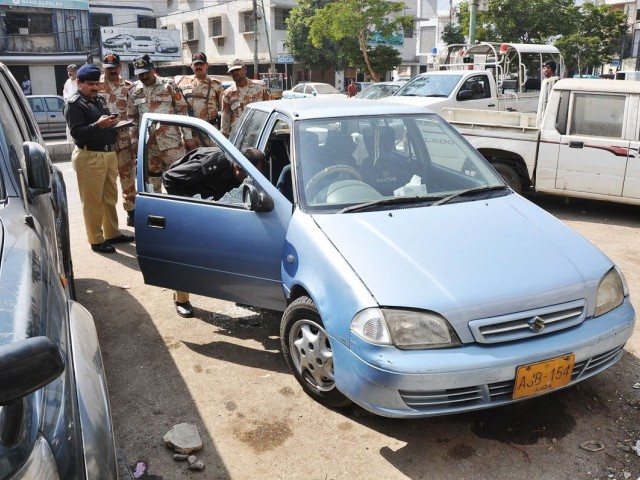 Police and Rangers officials inspect the car of a plastic surgeon who was gunned down near Tariq Road on Monday. PHOTO: MOHAMMAD AZEEM/EXPERSS/FILE