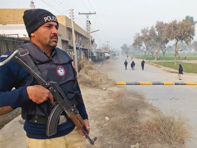 A policeman stands guard near the site of a bomb attack in Bannu. PHOTO: AFP