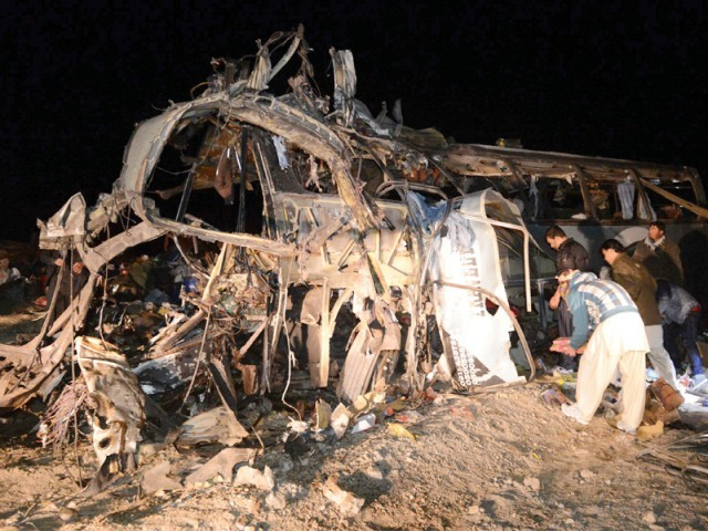 Security officials and rescue workers gather at the site of the bus bombing in Mastung. PHOTO: AFP