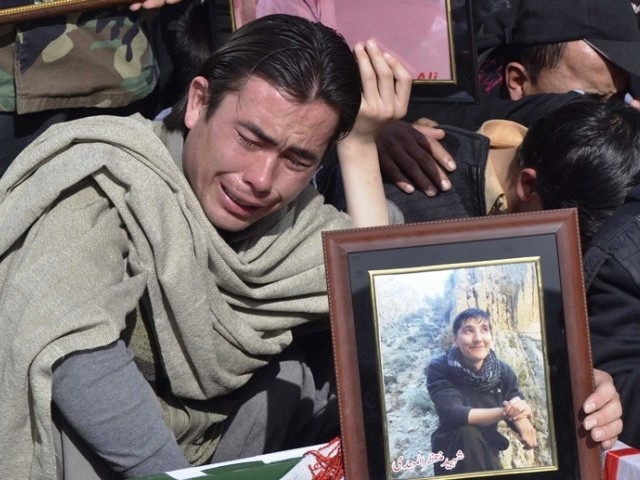 A man holds picture of his relative, a victim of Mastung bomb attack on a bus, beside the covered body, during a funeral in Quetta January 24, 2014. PHOTO: REUTERS