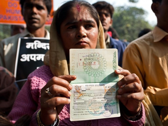A Hindu refugee from Pakistan shows her now-expired Indian visa page on her passport. PHOTO: AFP
