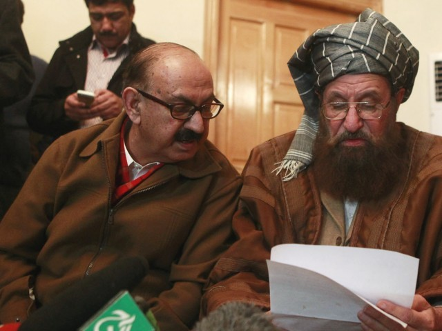 Maulana Samiul Haq (seated R), one of the Taliban intermediary, and Irfan Siddiqui, a government negotiator, discuss on a joint statement before a news conference in Islamabad February 6, 2014. PHOTO: REUTERS