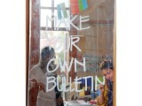 At the bacha bulletins corner, which is a project by LAAJVERD, one of the members is writing 'Make Your Own Bulletin'. PHOTOS: AYESHA MIR/EXPRESS