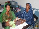 Two women from Thar watch as a child cries out. PHOTO: PPI