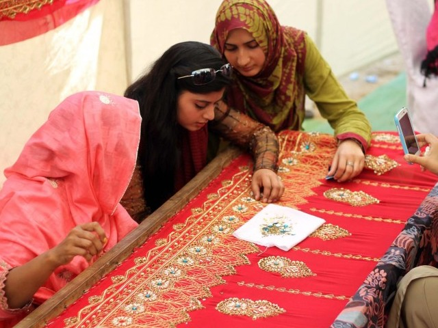 Students see how women workers embroidery clothes during a demonstration in Karachi university. PHOTO: PPI