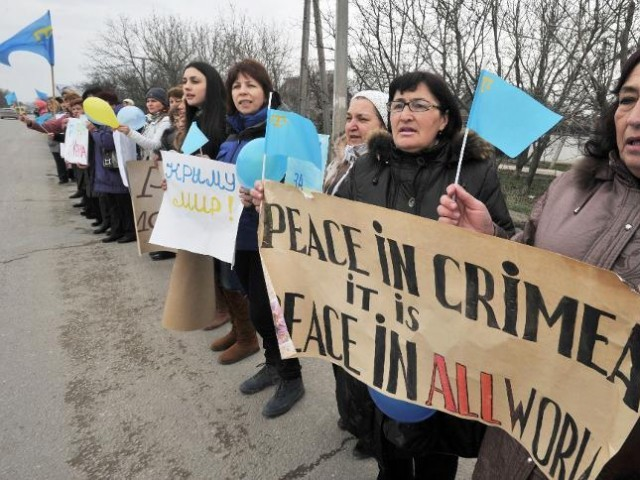 "Women hold Crimean Tatar flags and placards reading ""Peace in Crimea it is peace in all world"" during an anti-war rally in Simferopol on March 8, 2014. PHOTO: AFP"