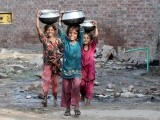Three little girls carry home pots full of water from a public tap in Gujjar Pur area of Lahore. PHOTO: PPI