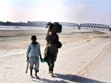A woman and her child cross the dried bed of the once might river Indus near Hyderabad. PHOTO: ONLINE