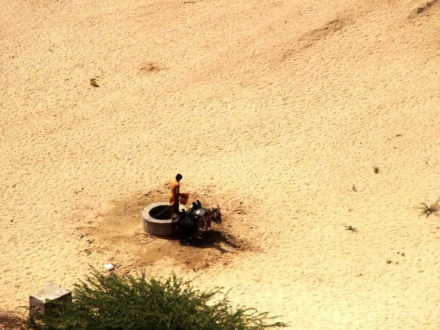 A man takes water out of a well in the parched Tharparkar desert. PHOTO: ONLINE