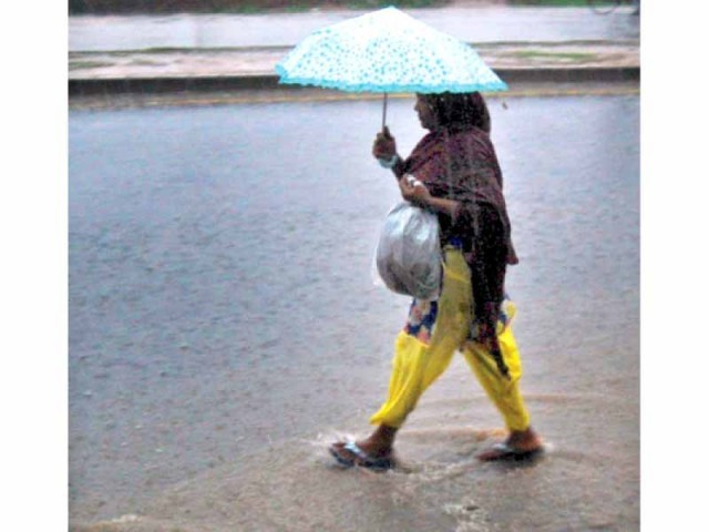 A woman splashes through rainwater accumulated on IJP Road. PHOTO: MUHAMMAD JAVAID/EXPRESS