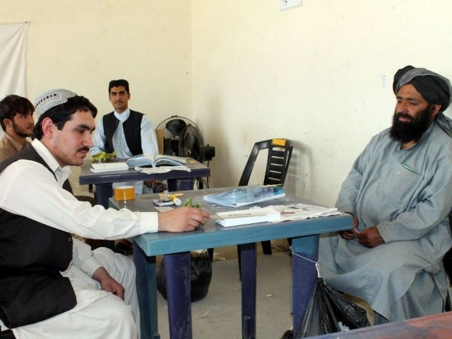 An Afghan man (R) waits to receive his identification card to vote in upcoming elections at a registration centre in Kandahar. PHOTO: AFP