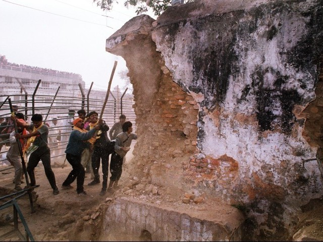In this December 6, 1992 photograph, rioters attack the wall of the 16th century Babri Masjid Mosque with iron rods at a disputed holy site in the city of Ayodhya. PHOTO: AFP/FILE
