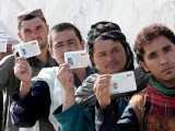 Afghan voters display their national identity cards as they queue to cast their votes at a local polling station in Kandahar. PHOTO: AFP