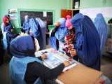 An Afghan voter is processed prior to casting her ballot at a polling station in Mazar-i-Sharif. PHOTO: AFP