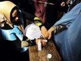 An Afghan election employee helps a voter to put her finger into an inkpot at a polling station in the northwestern city of Herat. PHOTO: AFP