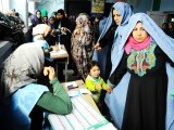 Afghan women receive their ballots to vote at a polling station in the northwestern city of Herat. PHOTO: AFP