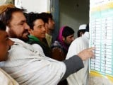 Afghan voters look at a candidate list as they lineup before casting their votes at a local polling station in Kandahar. PHOTO: AFP