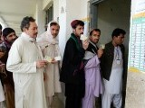 Afghan voters display their national identity cards as they lineup before casting their votes at a local polling station in Kandahar. PHOTO: AFP
