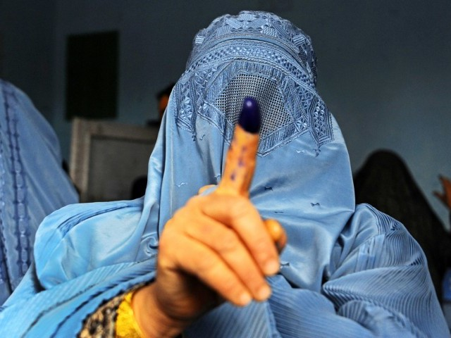 An Afghan woman shows her inked finger after voting at a polling station in the northwestern city of Herat. PHOTO: AFP