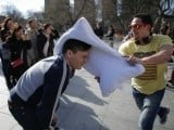 A man cringes as his friend smashes a pillow into his face at Washington Square Park in New York. PHOTO: REUTERS